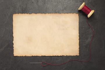 spool of thread and needle on slate stone
