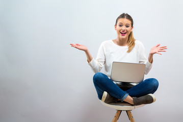 Surprised young woman using a laptop computer on a gray background