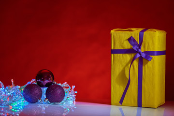 Beautiful yellow Christmas box with decorations on red background