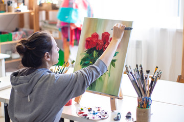 Girl artist paints a picture on canvas with a palette knife