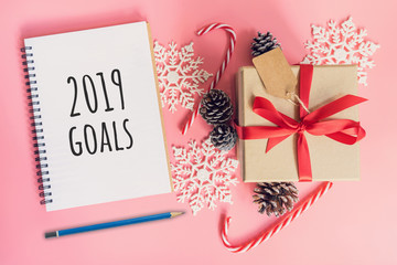 2019 New Year Goals, top view brown gift box, notebook and christmas decoration for new year on pink pastel color.