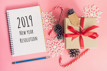 2019 New Year Resolution, top view brown gift box, notebook and christmas decoration for new year on pink pastel color.
