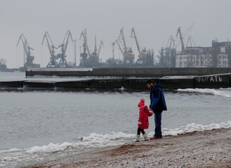 People rest on a beach in front of the Azov Sea port of Mariupol