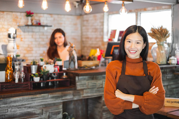 Young asian woman business owner at front of cafe/bar/restaurant/coffee and bakery shop