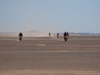 Motorcycle endurance drivers and dust in desert