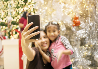 asian mother hand hold mobile with daughter fot take selfie photo