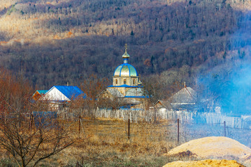 autumn village landscape with an Orthodox Church on a forest background