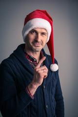 Man in santa hat raised his finger up