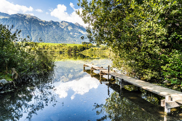 mountain lake in amsoldingen, peaceful, with footbridge and view of the berner alps, switzerland