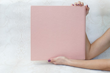 man hold a photo album photobook in the hands a woman holds a photobook sample photobook