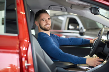 Brunette handsome man in blue sweater smiling in red car.
