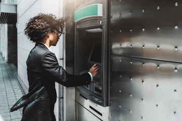 Side view of curly businessman in a formal suit and fancy sunglasses withdrawing money from a bank card using a street cash machine ATM, with a copy space place on the right for your logo or advert