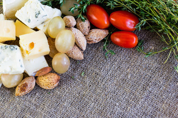Food background. Tasty snacks: cheese, grapes, almond and tomato.