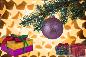 Christmas tree with pink ball and gift boxes on light decorative background