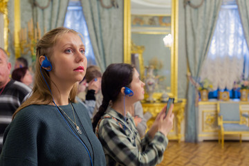 Students listening audioguide in tourist group. Russian museum
