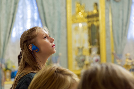 Portrait of girl with light hair listening audioguide in tourist group. Light blue wall of museum on the background