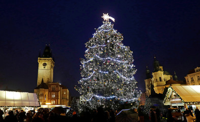 A Christmas tree is illuminated as people visit the traditional Christmas market at the Old Town Square in Prague