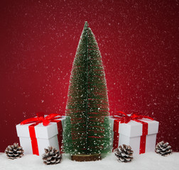 White gift boxes and fir tree on red background.