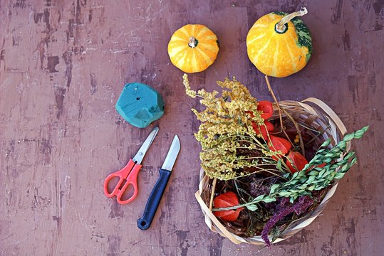 Materials for creating autumn floral compositions: decorative pumpkins, dried flowers and herbs in a wooden basket, floral sponge, scissors, knife. Holding creative workshops concept. Top view.