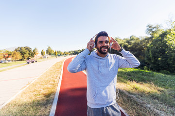 Handsome beard  man listening music using headphones and preparing for training