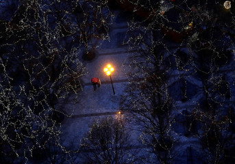People walk under trees decorated with Christmas lights at the Old Town Square in Prague