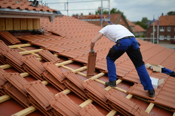 Obraz Dachdecker Bauarbeiter Mann auf Haus beim Ton Dachziegeln decken an der Arbeit - fototapety do salonu