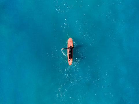 Surfer top of wave in ocean, top view aeria