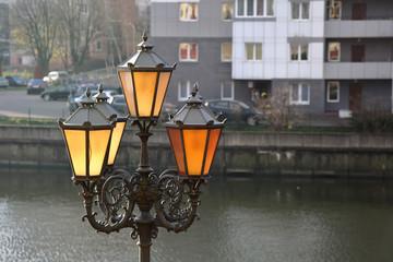Vintage iron lantern on the street of the modern city Fotomurales