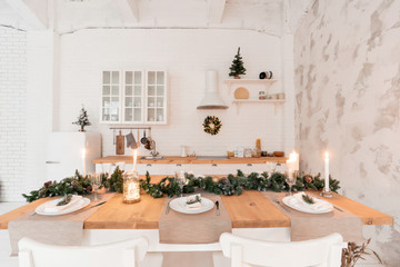 Loft style Apartment, large spacious living room with dining table and kitchen. Room with Christmas tree. Light white brick wall.