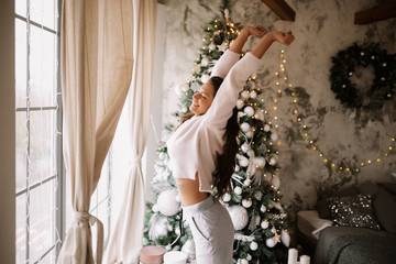 Charming girl dressed in white sweater and pants stands next to the New Year tree in front of the window and stretches up  in a cozy decorated room  with New Year's wreath