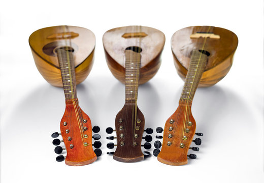 Three old mandolins rotated fingerboards to the camera. Isolated on a white background. Selective focus.