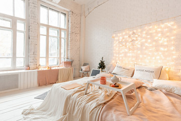 Christmas morning, Breakfast in bed, coffee and desserts. Loft style apartments. Bed in the bedroom, high large Windows. Brick wall with candles and Christmas tree. White color.