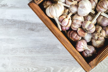 Fresh garlic in wooden box on a black stone surface, top view, copy space