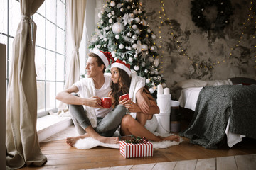 Happy guy and girl in white t-shirts and Santa Claus hats sit with red cups on the floor in front of the window next to the New Year tree, gifts and candles