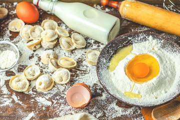 Ingredients and tools for baking and raw homemade italian ravioli, dumplings