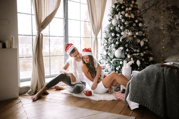 Happy guy and girl in white t-shirts and Santa Claus hats are sitting and hugging in the room on the floor in front of the window next to the New Year tree, gifts and candles