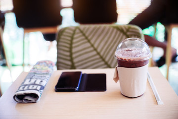 Ice coffee,smartphone and newspaper in coffee shop.