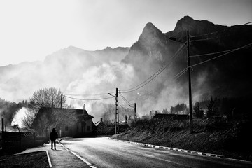 Beautiful misty landscape in well known Busteni mountain resort with Caraiman mountains in the background, Prahova Valley, Romania. Street photography, black and white creative image.
