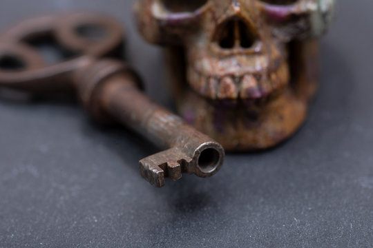 Old antique vintage metallic key and stone carved skull on natural stone background.
