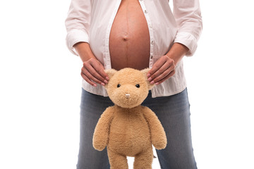 Pregnant girl holding a teddy bear by the ears on white background.