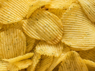 Popular american fast food, beer snack. Corrugated potato chips closeup. Texture. Background