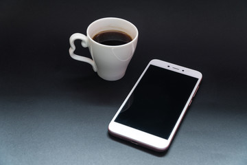 a cup of coffee and a telephone on a black background.