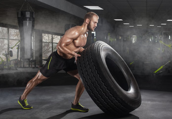 Young adult man flipping and rolling tire during exercise in the gym. Sports concept, fat burning and a healthy lifestyle.