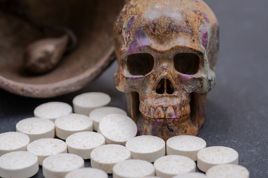 Concept for whom the bell tolls: stone carved skull, vintage antique bell and medical pills on natural stone background.