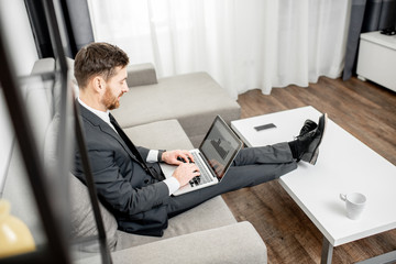 a17930a5cf52 Elegant businessman dressed in the suit working with laptop on the couch at  home or comfortable