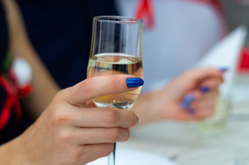 Guest holds glass with bubbly champagne in weddind. Wedding details in close-up view.