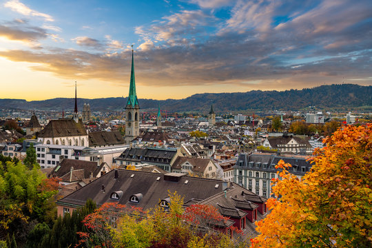 Beauitful sunset over Zurich in autumn with Fraumünster church in the centre and mountains in the background