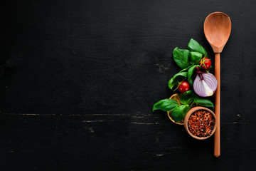 Wall Mural - Fresh basil and spices. On a black wooden background. Top view. Free copy space.
