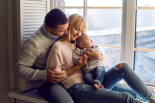 family in warm sweaters with his son sitting on the window in the winter