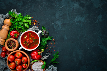 Tomato soup with onion, cucumber and paprika. Top view. On a black background. Free space for text.